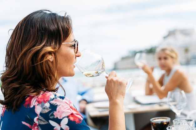 Woman drinking wine with other people on the terrace of a beachfront restaurant