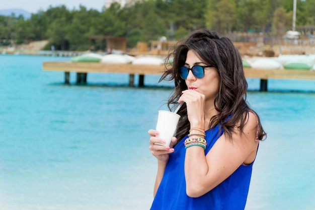Woman drinking with sunglasses