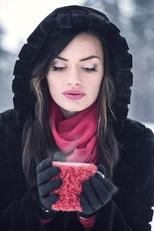 여자는 겨울에 컵에서 뜨거운 음료를 마신다