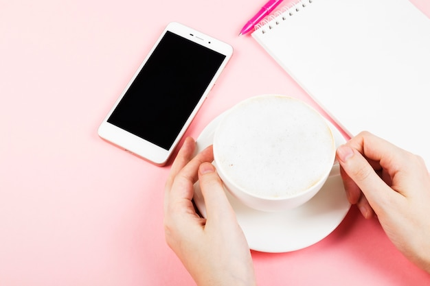 Woman drinks cappuccino. concept morning planning (cappuccino, notebook, pen, phone). copy space. food space