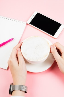 Woman drinks cappuccino. concept morning planning (cappuccino, notebook, pen, phone)