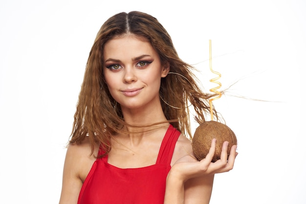 Woman drinks coconut cocktail through a straw lifestyle red t-shirt light background.