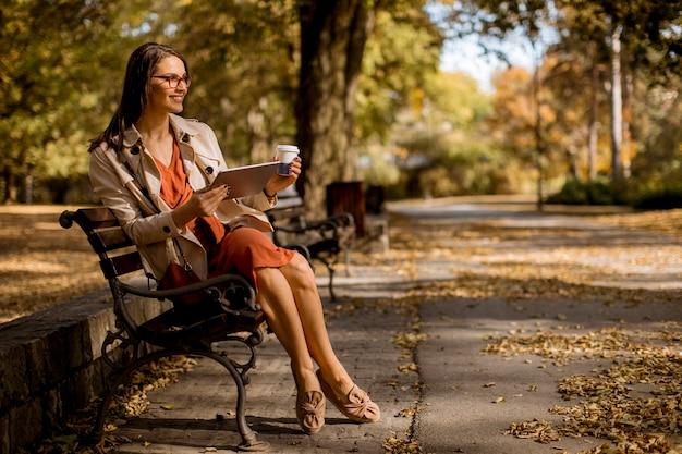 Женщина пьет кофе и сидит на скамейке в парке в осеннюю погоду, используя планшетный пк и проверяя социальные сети.