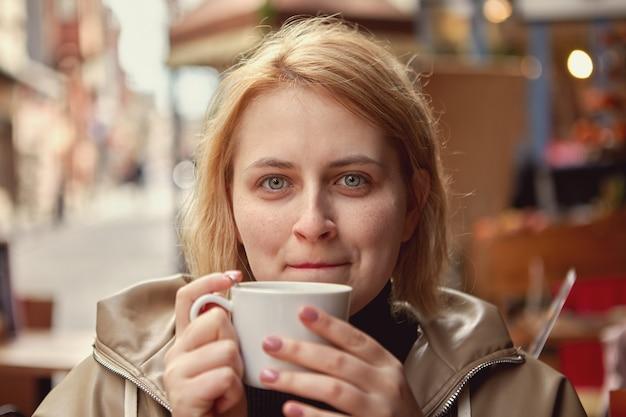 Женщина пьет кофе за столиком в уличном кафе в стамбуле