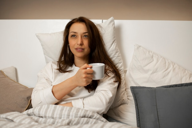 Woman drinks coffee in bed and watches tv series