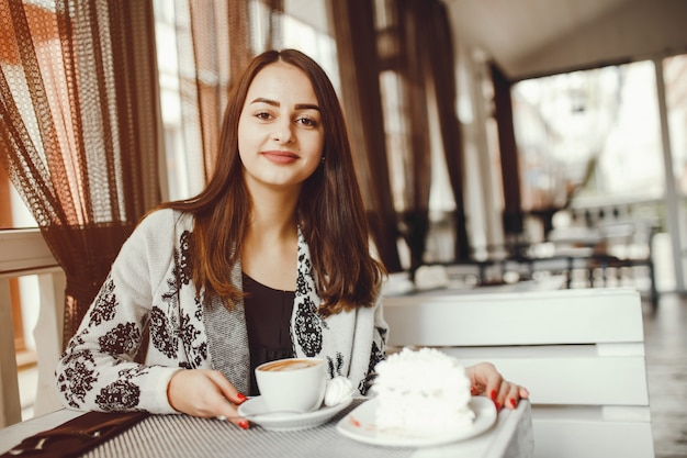 The woman drinks coffee at the cafe