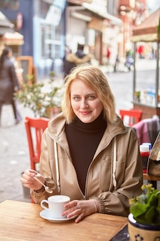 Женщина пьет кофе в стамбуле за столом в уличном кафе зимой.