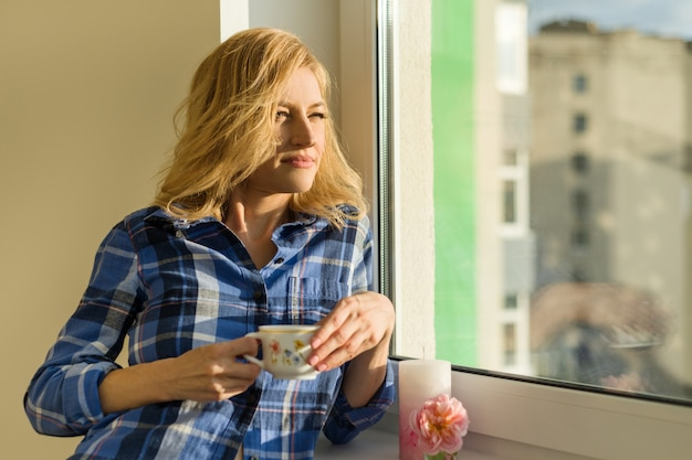 Woman drinks coffee, looks out the window at home