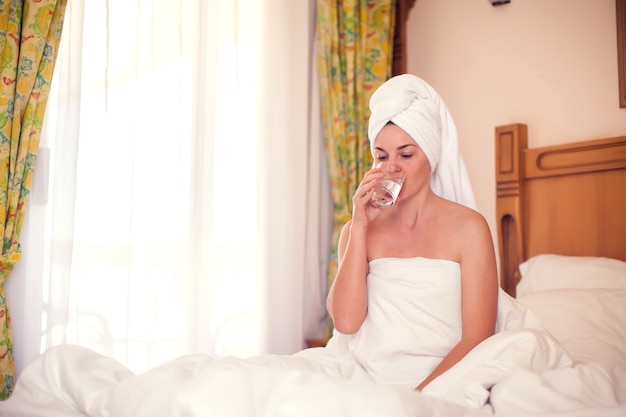 女性は朝、新鮮な水を飲みます。人、医療、ライフスタイルのコンセプト