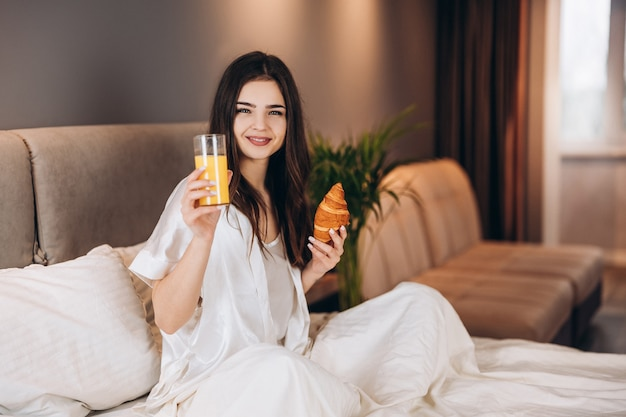 Woman drinks orange juice in bed. breakfast in bed. a model in white pajamas sits in bed and holds a glass of orange juice.