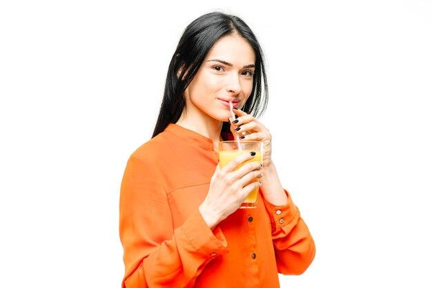 女性は白地にオレンジジュースを飲む