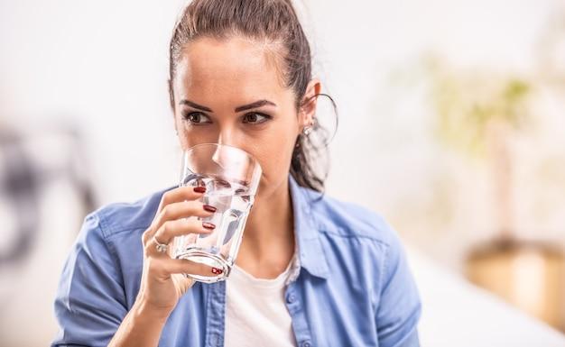 Женщина пьет чистую воду из стакана в руке.