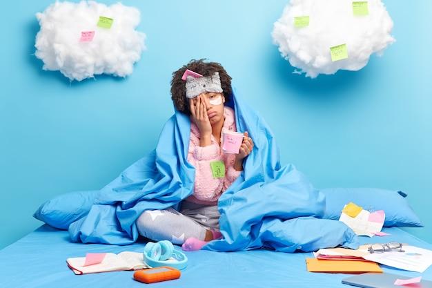 Женщина пьет освежающий кофе, работала всю ночь над проектом, работает на расстоянии, одетая в пижаму, позирует на кровати, накрытой теплым одеялом