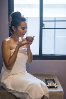 Женщина пьет чай после массажа в спа