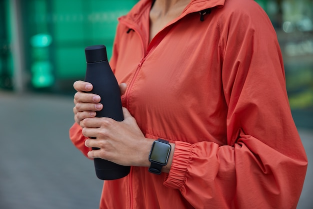 Woman drinks water after hard training outdoors holds bottle of water uses smartwatch dressed in windbreaker feels thirsty after sport practice poses on blurred
