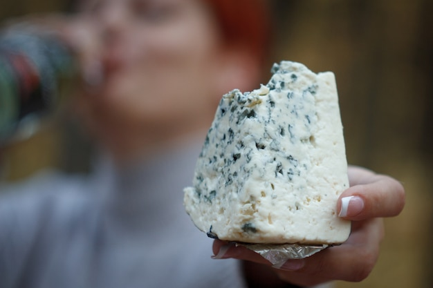 Woman drinks wine from a bottle and holds in her hand a large bitten piece of cheese