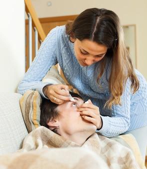 Женщина капает глазные капли человеку
