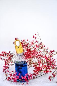 Женщина капает эфирное масло розы стеклянная пипетка косметического масла и сушеных цветов и трав на белом