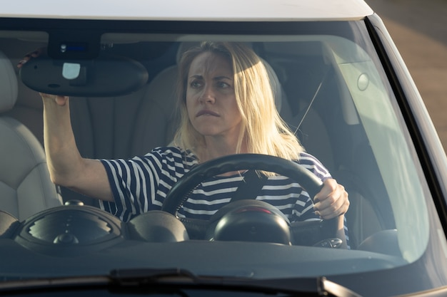 Woman driver beginner worried of problem with parking look in back view mirror afraid of car crash