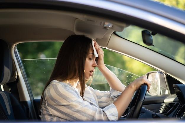 Женщина-водитель, которой жарко во время аномальной жары в машине, вытирает пот со лба