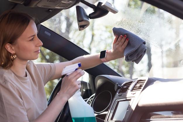 女性ドライバーが車のフロントガラスをスプレーでクレンジングし、マイクロファイバーでほこりや汚れを拭き取ります。