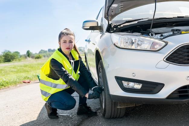 Woman driver fixing changed wheel on roadside
