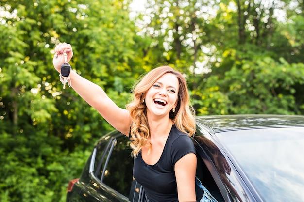 Водитель женщины держа ключи от машины за рулем своего нового автомобиля смеющаяся молодая девушка.