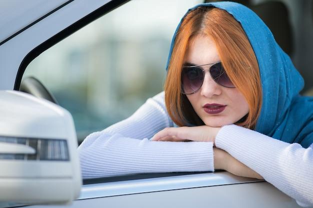 Водитель женщины в шарфе и солнечных очках смотря вне переднее окно автомобиля.