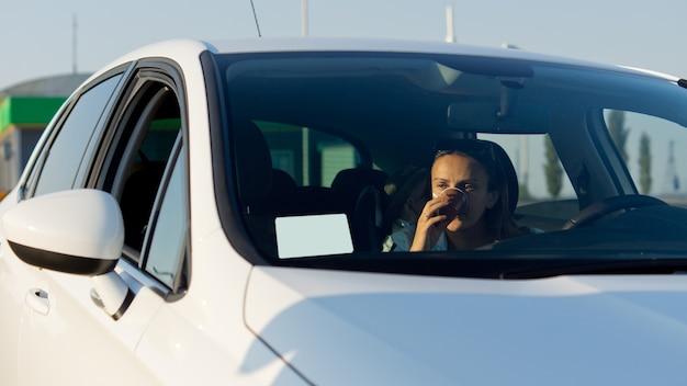 그녀는 그녀의 차 앞 유리에 종이의 빈 시트를보고 그녀의 얼굴에 그녀의 손으로 차에 여자 드라이버