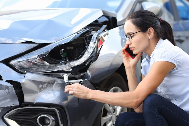 여성 운전자가 자동차 사고 후 난파된 자동차 옆에서 전화로 보험 대리인에게 전화를 걸고 있습니다