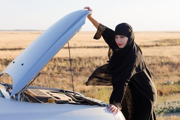 Водитель женщина смотрит на сломанный двигатель автомобиля, держа капот рукой