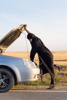 Женщина-водитель впервые открывает капот автомобиля.
