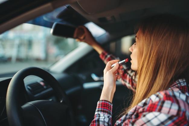자동차에 립스틱으로 그녀의 입술을 페인트하는 여성 드라이버