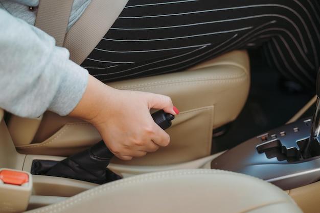 車の中でハンドブレーキを引く女性ドライバー。