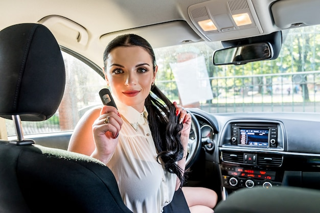 자동차 안에 자동차 키를 보여주는 여자 드라이버