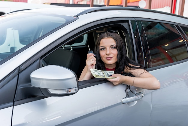 Woman driver showing dollars and car keys from window
