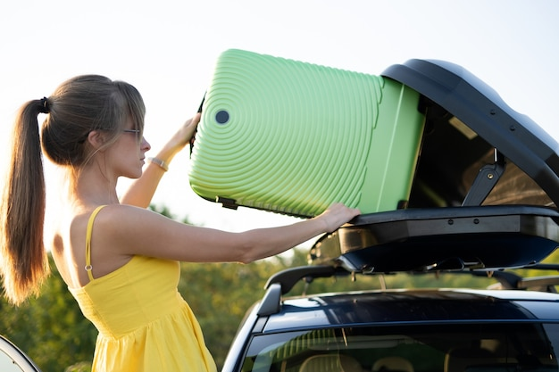 Woman driver taking green suitcase from car