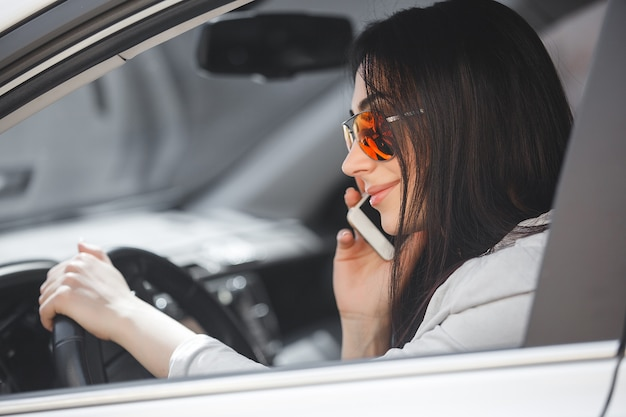 Woman driver talking on phone. beautiful girl in the car. lady driving a white car.