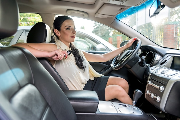 Woman driver testing new car and holding key