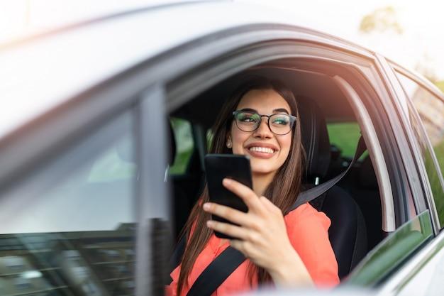車でスマートフォンを使用して女性ドライバー。