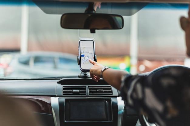 車の運転中に携帯電話でgpsナビゲーションを使用する女性ドライバー。