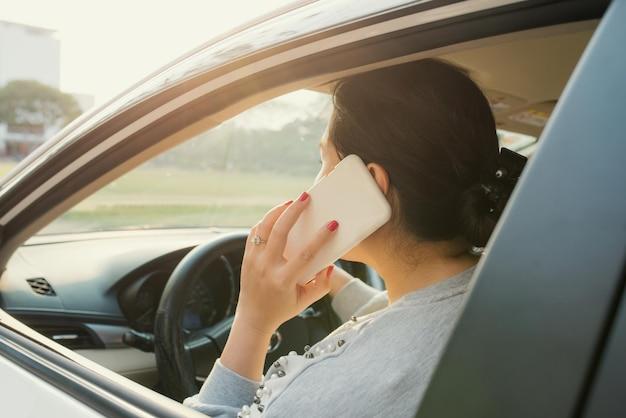 車の運転中に携帯電話を使用する女性ドライバー