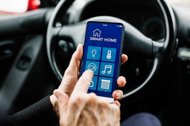 자동차의 스마트폰에서 스마트 홈 앱을 사용하는 여성 운전자 - 사물 인터넷(iot) 개념