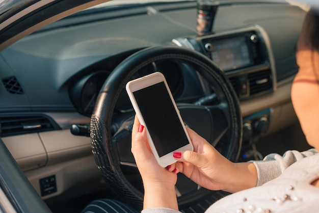 교통 체증 동안 자동차에서 스마트 폰을 사용하는 여성 운전자, 디자인 목적으로 빈 화면.