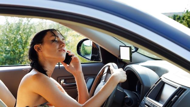 운전대에 손을 얹은 여성 운전자가 휴대 전화를 사용하고 대화를 들으면서 고개를 뒤로 젖혀 집중력을 잃습니다.