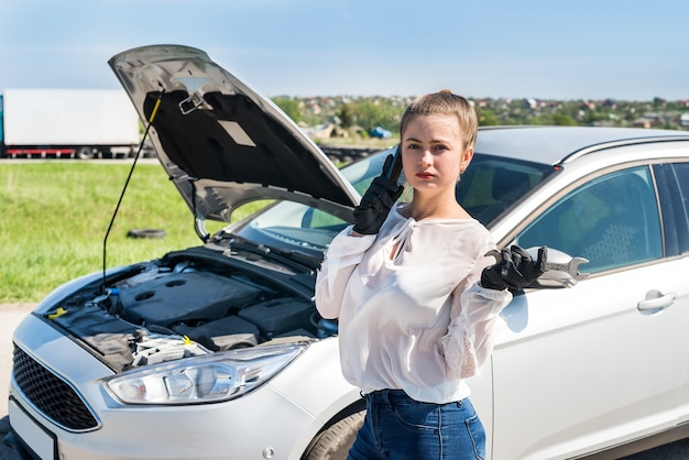 Woman driver with spanners calling for help