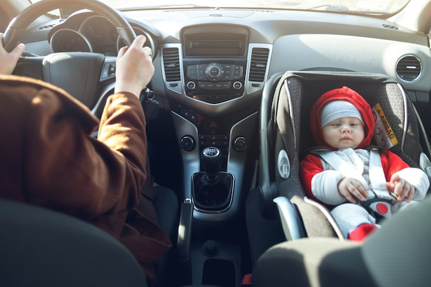 Женщина ведет машину, а ее маленький ребенок сидит в переднем детском автокресле, пристегнутый ремнем безопасности.