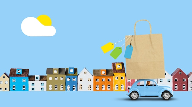 지붕에 종이 봉지를 쇼핑하고 파란 차를 운전하는 여성은 거리에 미니어처 주택이있는 매장 판매에서 돌아옵니다. 공간 복사