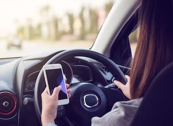 Женщина за рулем и с помощью смартфона на дороге