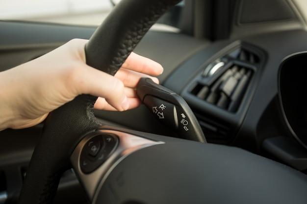 車を運転し、方向指示器スイッチを使用している女性